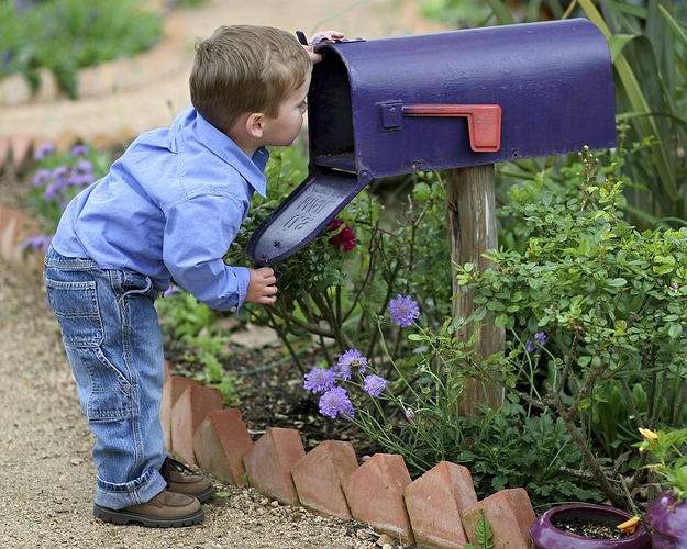 little-boy-looking-in-mailbox